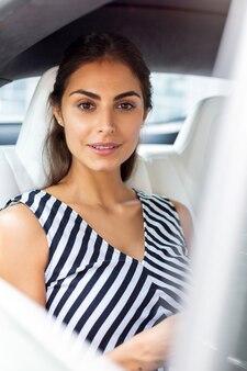 Sitzen im auto. schöne junge frau mit schwarzer und weißer bluse, die im auto sitzt