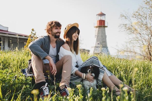 Sitzen im gras junge stilvolle hipster-paar in der liebe mit hund in der landschaft, sommer-stil boho mode, romantisch