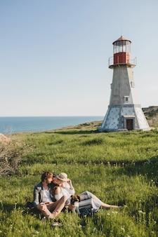Sitzen im gras junge stilvolle hipster-paar in der liebe mit hund in der landschaft zu fuß