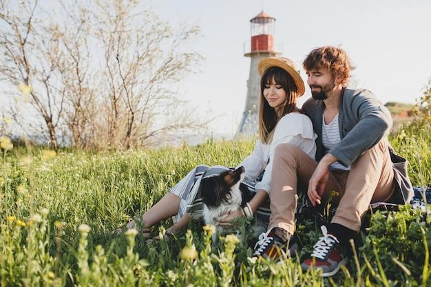 Sitzen im gras, junges stylisches hipster-paar verliebt in den hund auf dem land