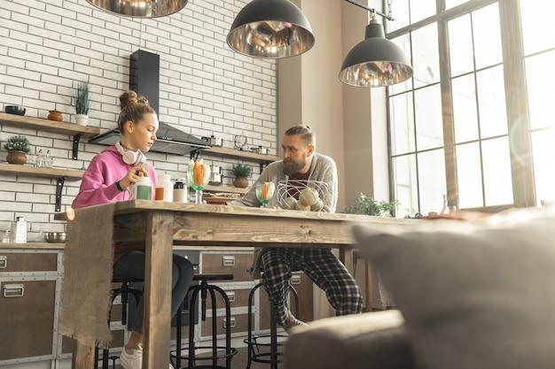 Sitzen in der küche. liebevoller gutaussehender vater und tochter sitzen in der küche und essen zusammen