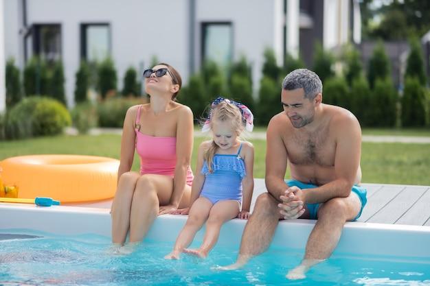 Sitzen in der nähe des pools. eltern und ihre schöne tochter sitzen an einem heißen sommertag in der nähe des swimmingpools