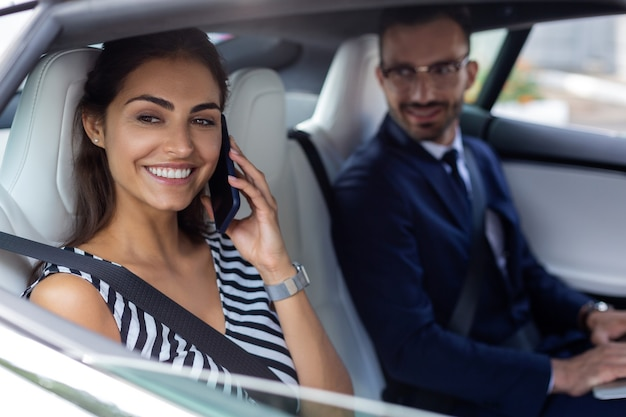 Sitzen in der nähe von ehemann. dunkeläugige, ansprechende frau, die am telefon spricht, während sie neben ihrem ehemann im auto sitzt