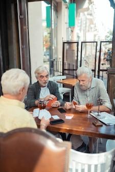 Sitzen vor der kneipe. drei ältere männer im ruhestand, die autos spielen, während sie vor der kneipe sitzen