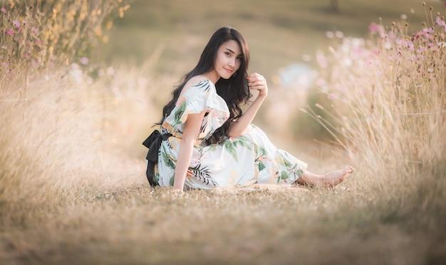 Sitzende aufstellung des schönen asiatischen frauenmädchens in der parkblumenbild-artweinlese