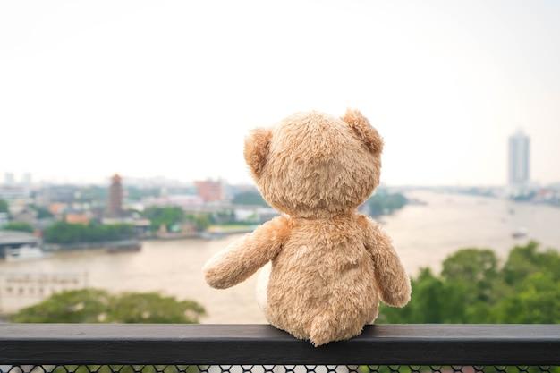 Sitzende flussansicht des einsamen teddybären. (chao phraya fluss in bangkok stadt)