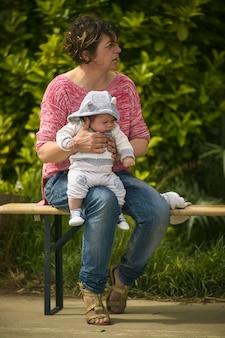 Sitzende frau in einem park hält ein kleines kind im arm
