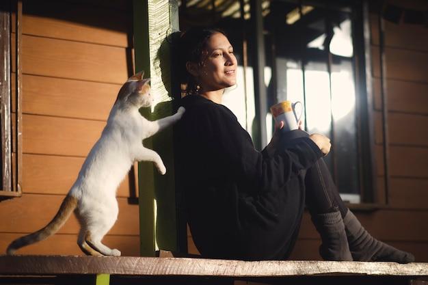 Sitzende frau trägt haushaltskleidung, trinkt kaffee und spielt mit ihrer katze