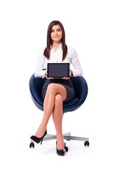 Sitzende geschäftsfrau, die ein leeres digitales tablett mit schwarzem bildschirm hält
