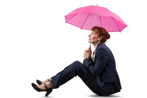 Sitzende geschäftsfrau, die rosa regenschirm hält