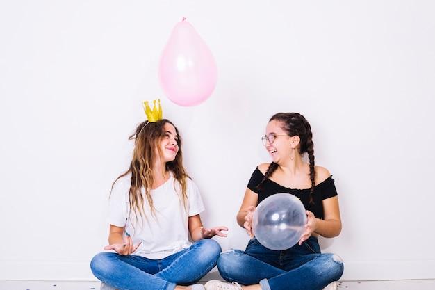 Sitzende jugendliche, die mit ballonen spielen