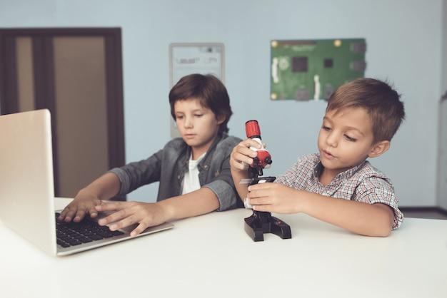 Sitzende jungen mit laptop und mikroskop zu hause.
