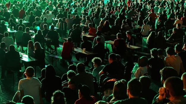 Sitzende leute, die nachts an einem öffentlichen ort fußball gucken