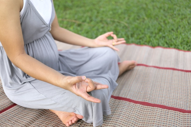 Sitzende meditation der schwangeren frauen im park.