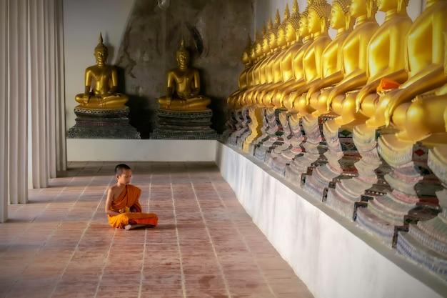 Sitzende meditation des asiatischen mönchneophyten im tempel ayutthaya, thailand.