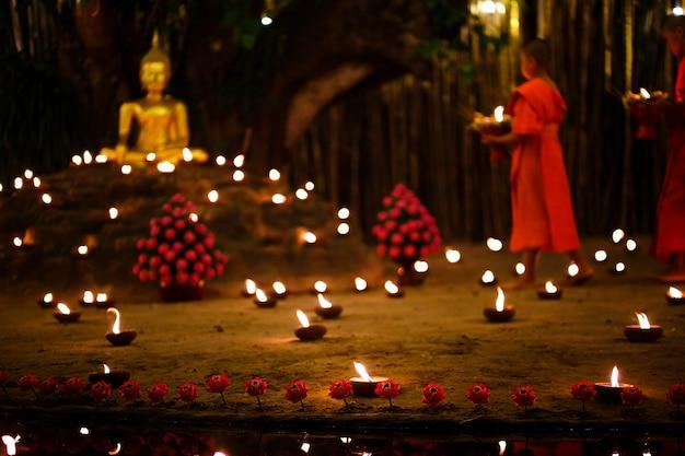 Sitzende mönche meditieren nachts mit vielen kerzen im thailändischen tempel