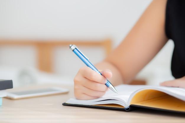 Sitzende studie der nahaufnahmehandasiatischen frau und lernen, notizbuch und tagebuch auf tabelle zu schreiben