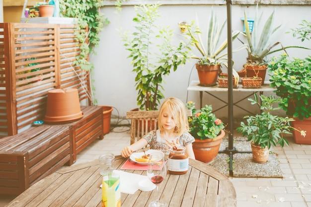 Sitzende tabelle des weiblichen kindes im freien, die frühstückt