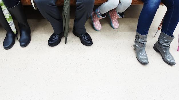 Sitzende tragen jeweils unterschiedliche schuhe in einem zug.