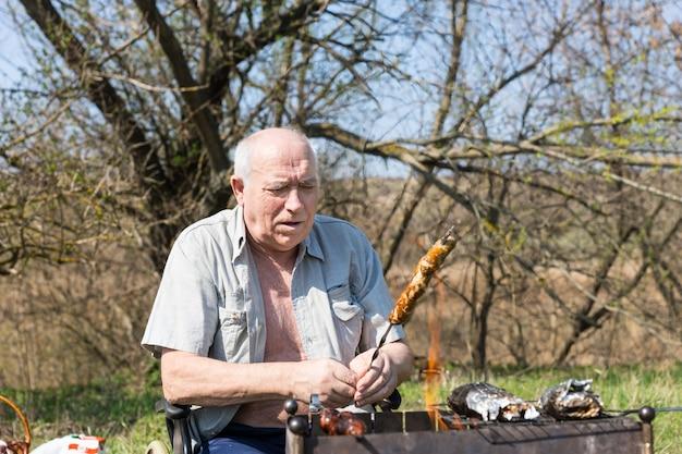 Sitzender älterer mann, der fleisch am stock für seine mahlzeit ernsthaft auf dem campingplatz allein brät.