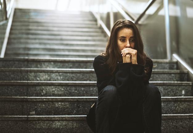 Sitzender blick der frau besorgt auf dem treppenhaus