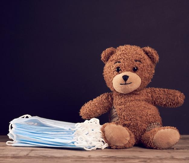 Sitzender brauner teddybär und medizinische einwegmaske auf einer schwarzen tafel