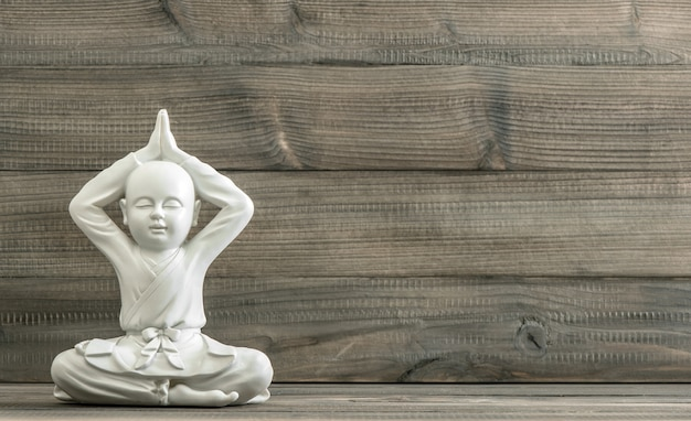 Sitzender buddha. weiße mönchsstatue auf hölzernem hintergrund. meditation. entspannend. getöntes bild im retro-stil