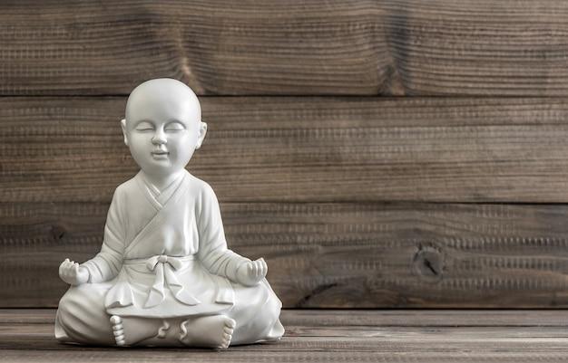 Sitzender buddha. weiße statue auf hölzernem hintergrund. entspannendes konzept