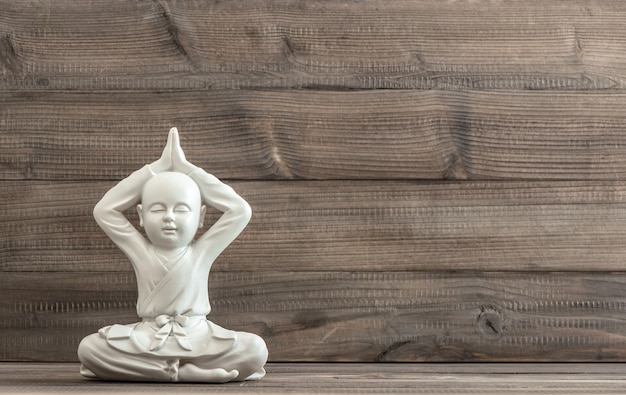 Sitzender buddha. weiße statue auf hölzernem hintergrund. meditation