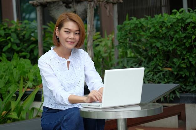 Sitzender gebrauchslaptop der asiatischen geschäftsfrau am park im freien