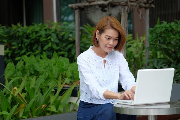 Sitzender gebrauchslaptop der asiatischen geschäftsfrau am park