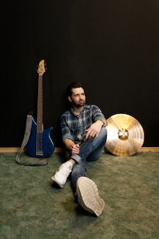 Sitzender gitarrist an der wand gelehnt