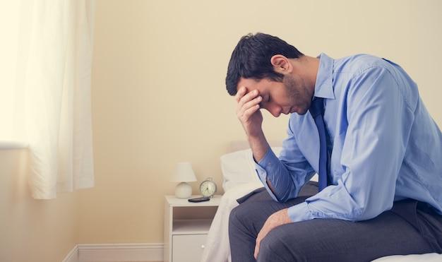 Sitzender kopf des deprimierten mannes in den händen auf seinem bett