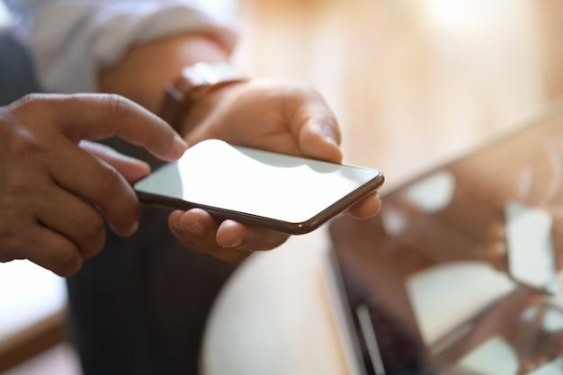 Sitzender mann bei der verwendung des mobilen smartphones