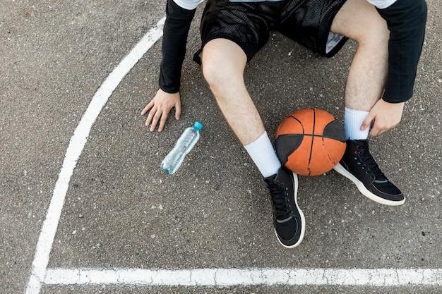 Sitzender mann der draufsicht mit basketball