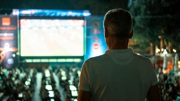 Sitzender mann, der nachts an einem öffentlichen ort fußball guckt
