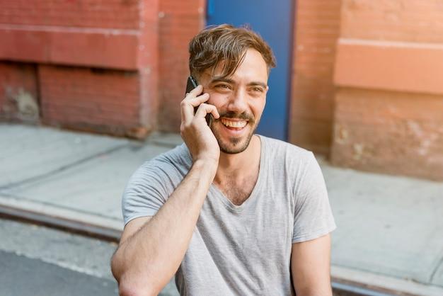 Sitzender mann, der über das telefon spricht