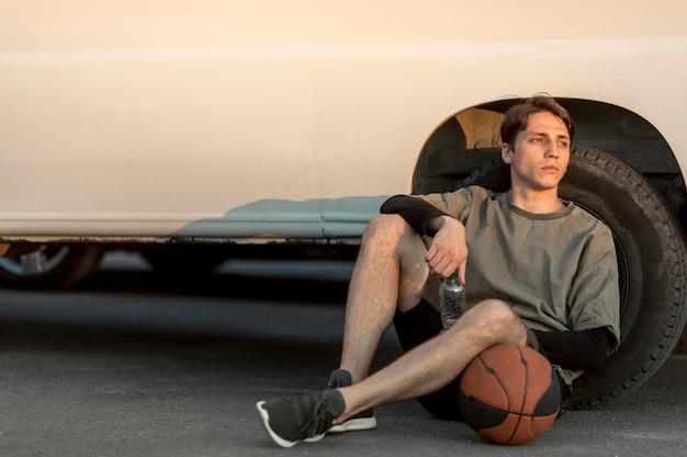 Sitzender mann der vorderansicht mit basketball