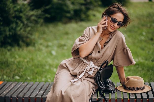 Sitzender park der jungen frau unter verwendung des telefons