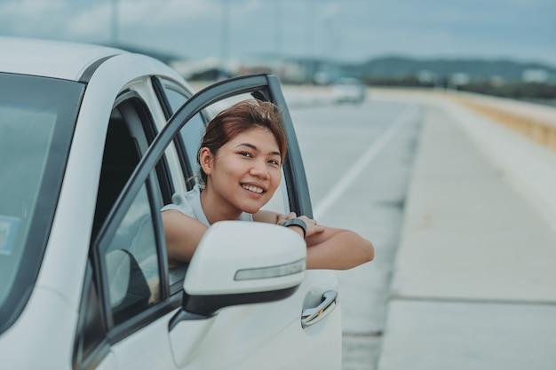 Sitzender pkw der asiatischen frau im sommerreiseurlaub. reisen konzept. entspannen und genießen