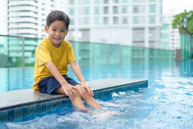 Sitzender swimmingpool des glücklichen asiatischen jungen