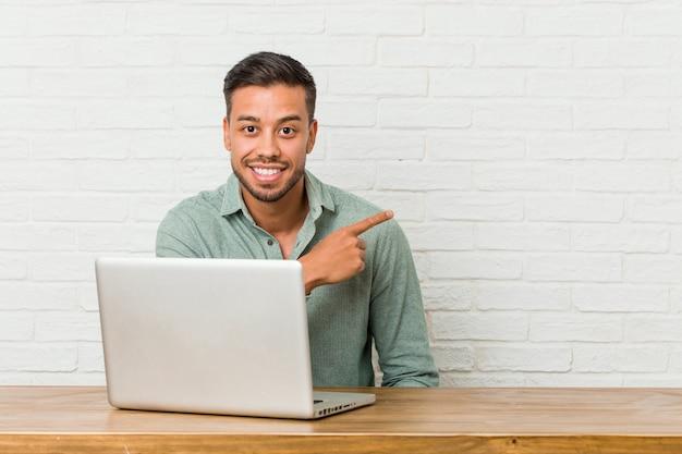 Sitzendes arbeiten des jungen philippinischen mannes mit seinem laptop, der beiseite lächelt und zeigt und etwas am freien raum zeigt.