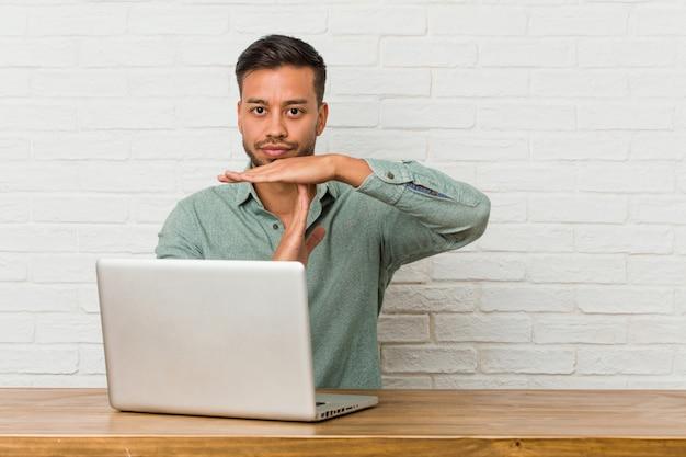 Sitzendes arbeiten des jungen philippinischen mannes mit seinem laptop, der eine auszeitgeste zeigt.