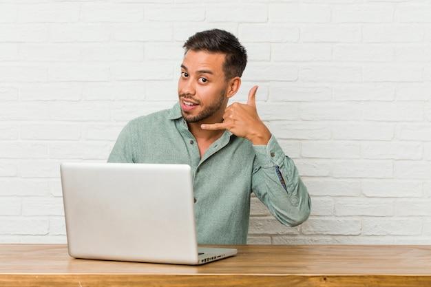 Sitzendes arbeiten des jungen philippinischen mannes mit seinem laptop, der eine handyanrufgeste mit den fingern zeigt