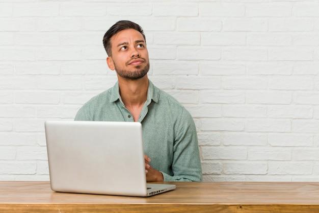 Sitzendes arbeiten des jungen philippinischen mannes mit seinem laptop, der plan im verstand, eine idee gründend bildet.