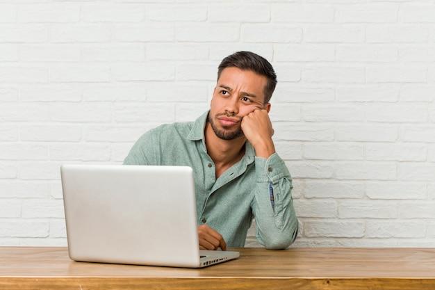 Sitzendes arbeiten des jungen philippinischen mannes mit seinem laptop, der traurig und nachdenklich sich fühlt und copyspace schaut.