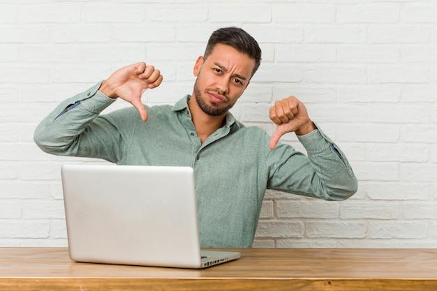 Sitzendes arbeiten des jungen philippinischen mannes mit seinem laptop, der unten daumen zeigt und abneigung ausdrückt.