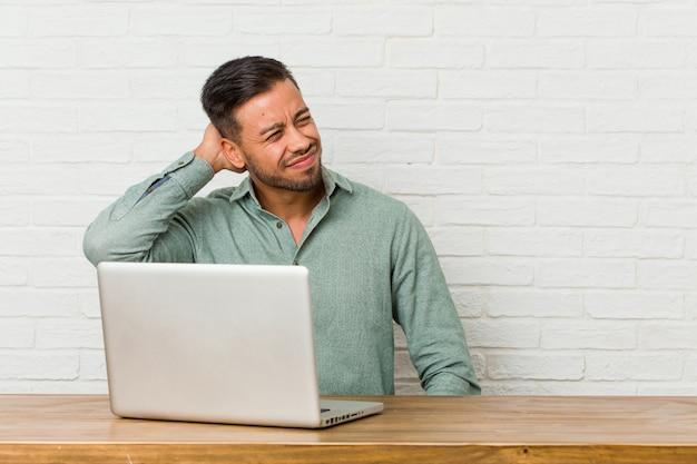 Sitzendes arbeiten des jungen philippinischen mannes mit seinem laptop, der zurück vom kopf berührt, eine wahl denkt und trifft.