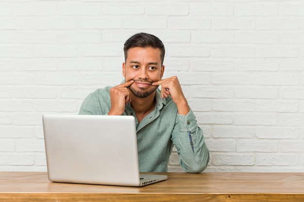 Sitzendes arbeiten des jungen philippinischen mannes mit seinem laptop, der zwischen zwei wahlen zweifelt.