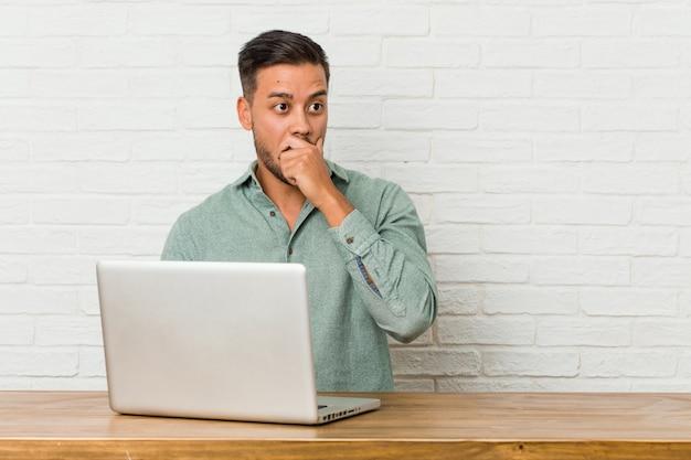 Sitzendes arbeiten des jungen philippinischen mannes mit seinem laptop entsetztes zeigen mit den zeigefingern auf einen kopienraum.